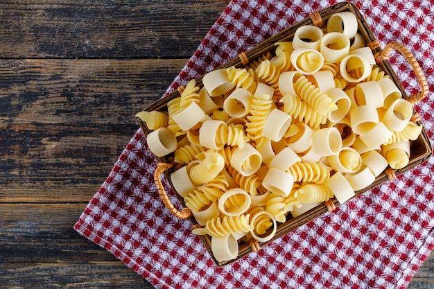 Vue de dessus des pâtes macaroni dans un panier sur un tissu de pique-nique et un fond en bois. espace horizontal pour le texte