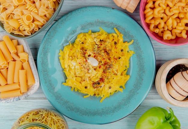 Vue de dessus des pâtes macaroni en plaque entourée de pâtes crues