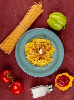 Vue de dessus des pâtes macaroni en plaque avec des tomates
