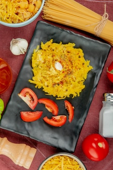 Vue de dessus des pâtes macaroni et tranches de tomate en plaque avec différentes pâtes