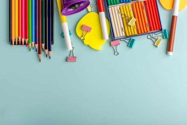 Vue de dessus des pâtes à modeler colorées avec des crayons de couleur sur le livre bleu des enfants de l'école de couleur bureau enfants