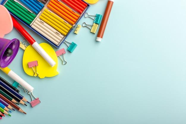 Vue de dessus des pâtes à modeler colorées avec des crayons de couleur sur le mur bleu couleur école enfants livre pour enfants