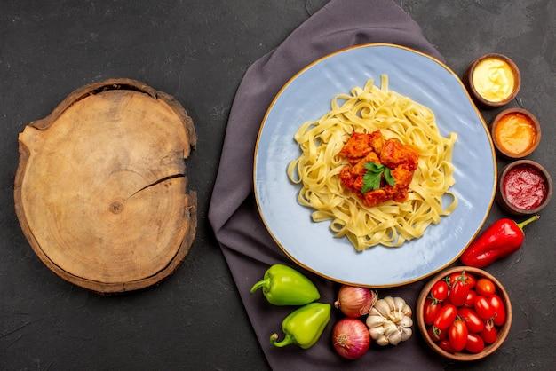 Vue de dessus des pâtes sur une nappe assiette bleue de pâtes appétissantes bol de sauces tomates ail oignon boule de poivre sur la nappe violette et planche de bois sur la table
