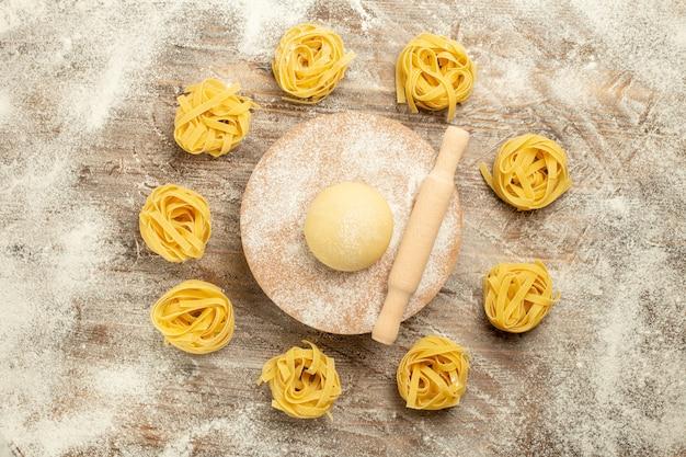 Vue de dessus pâtes de pâte crue avec de la farine sur fond de bois pâte alimentaire repas pâtes