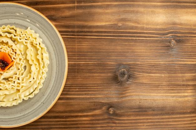 Vue de dessus pâtes de pâte crue formé à l'intérieur de la plaque sur la table brune pâtes alimentaires crues de la pâte de repas