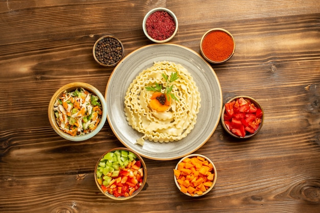 Vue de dessus pâtes de pâte crue formé avec des légumes et des assaisonnements sur la pâte de table brune pâtes alimentaires crues