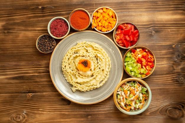 Vue de dessus pâtes de pâte crue formé avec des légumes et des assaisonnements sur la pâte de table brune repas de pâtes alimentaires crues