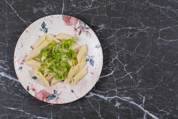 Vue de dessus. pâtes penne avec sauce verte sur plaque blanche.