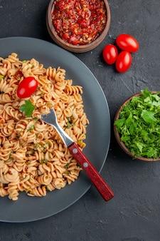 Vue de dessus des pâtes rotini avec fourchette de tomates cerises sur assiette persil et sauce tomate dans des bols tomates cerises sur surface sombre