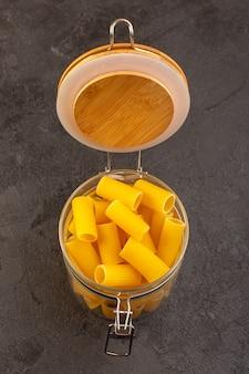 Une vue de dessus pâtes sèches italiennes crues jaune à l'intérieur bol isolé sur l'obscurité