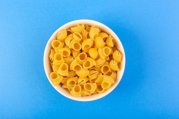 Une vue de dessus des pâtes sèches italiennes formées de petites pâtes crues jaunes à l'intérieur d'un bol rond de couleur crème isolé sur le fond bleu des pâtes alimentaires spaghetti italien