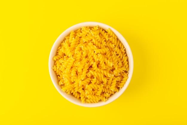 Une vue de dessus des pâtes sèches italiennes formées de petites pâtes crues jaunes à l'intérieur d'un bol rond de couleur crème isolé sur le fond jaune des pâtes alimentaires spaghetti italien