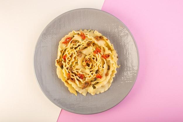 Une vue de dessus des pâtes avec de la viande et des légumes cuits à l'intérieur de la plaque grise sur blanc-rose