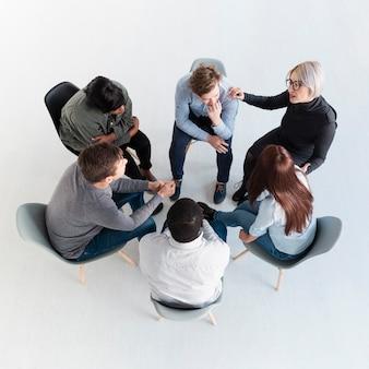 Vue de dessus des patients en réadaptation debout en cercle et parlant