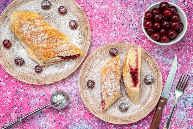 Vue de dessus de la pâtisserie aux cerises délicieuses et sucrées en tranches avec des cerises aigres fraîches à l'intérieur des assiettes sur le bureau de couleur biscuit sucré