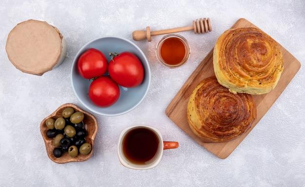 Vue de dessus de la pâtisserie traditionnelle azerbaïdjanaise gogal sur une planche de cuisine en bois avec des olives sur un bol en bois avec des tomates fraîches sur un bol sur un fond blanc