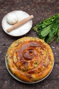 Vue de dessus pâtisserie verte cuite ronde à l'intérieur de la plaque blanche avec de la farine et des verts repas de bureau repas pâtisserie déjeuner verts