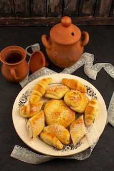 Vue de dessus des pâtisseries et des croissants à l'intérieur de la plaque blanche sur le noir