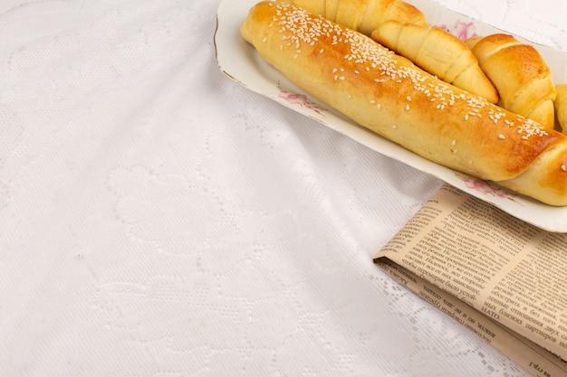 Vue de dessus des pâtisseries avec des croissants à l'intérieur de la plaque sur le sol blanc