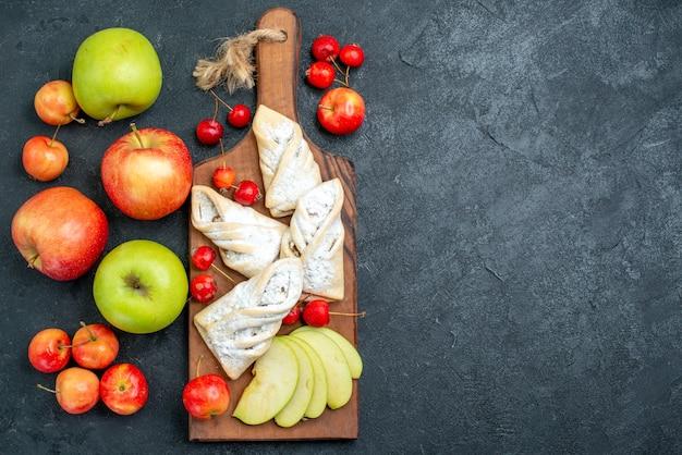 Vue de dessus des pâtisseries fruitées sucrées avec des fruits frais sur la surface gris foncé biscuit aux fruits tarte au sucre sucré