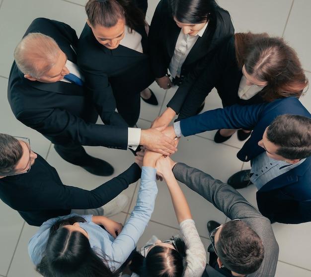 Vue de dessus. patron et équipe commerciale faisant une pile de mains. le concept d'unité