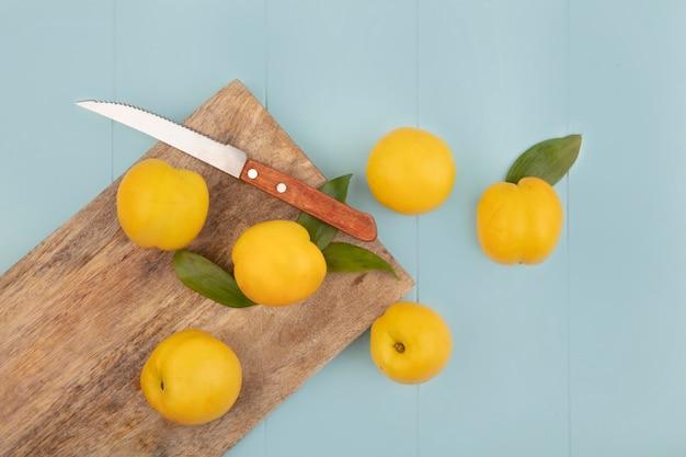 Vue de dessus des pêches jaunes fraîches isolées sur une planche de cuisine en bois avec un couteau sur fond bleu