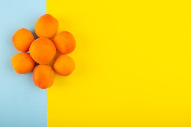 Une vue de dessus les pêches orange aigre savoureux fœtus frais bordés sur la glace-fond bleu-jaune fruits jus d'été exotique
