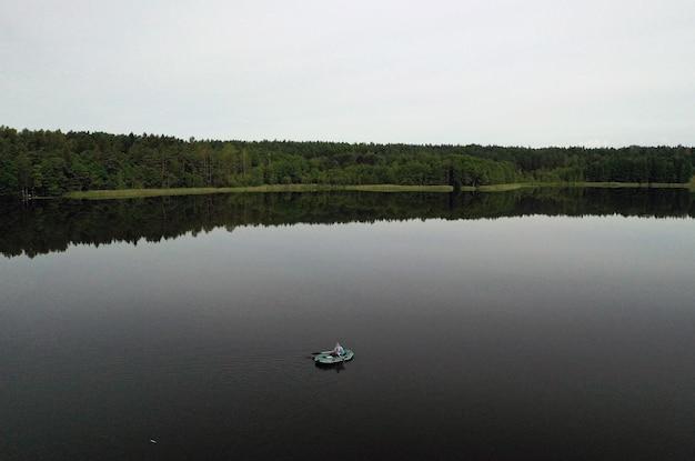 Vue de dessus d'un pêcheur solitaire sur un bateau tôt le matin à la pêche sur le lac