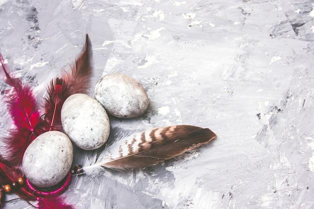 Vue de dessus peint des oeufs de pâques avec un effet pierre et des plumes brillantes