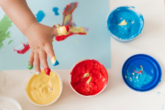 Vue de dessus de la peinture et des mains d'enfant