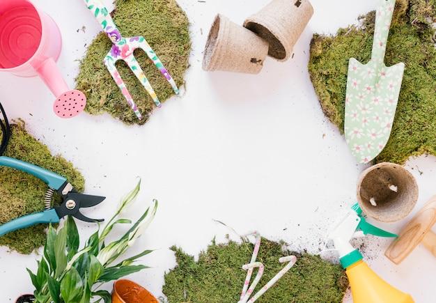 Vue de dessus pelle; fourchette de jardinage; sécateur; arrosoir; gazon; vaporisateur sur fond blanc