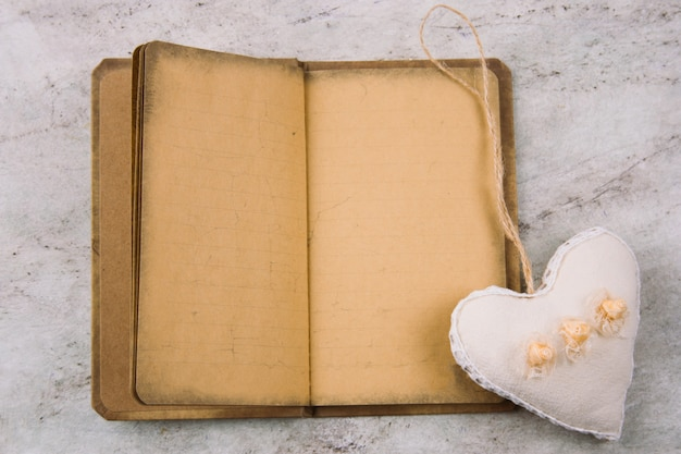 Vue de dessus en peluche coeur et papier vintage cahier ouvert sur fond de marbre