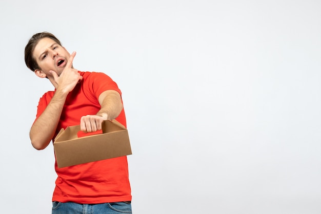 Vue de dessus de la pensée jeune homme en chemisier rouge tenant des commandes sur un mur blanc