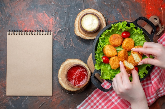 Vue de dessus des pépites de poulet dans un cahier de casserole sur un mur rouge foncé