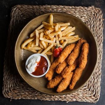Vue de dessus des pépites de poulet avec frites et tomates et sous dans des plats en argile