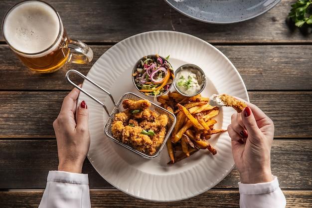 Vue de dessus des pépites de poulet panées avec salade de frites et une bière servie dans une assiette