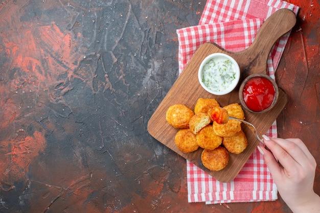 Vue de dessus des pépites de poulet sur une planche de bois avec une fourchette à sauces dans une main féminine sur un espace libre de table sombre