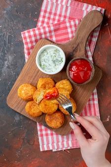 Vue de dessus des pépites de poulet sur une planche à découper avec une fourchette à sauces dans une main féminine sur une table sombre