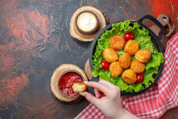 Vue de dessus des pépites de poulet et des sauces sur une planche à découper une pépite dans une main de femme sur un mur rouge foncé