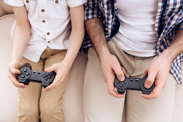 Vue de dessus. père avec fils joue le jeu en utilisant des contrôleurs de jeu.