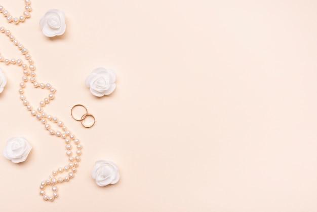 Vue de dessus perles élégantes avec bagues de fiançailles
