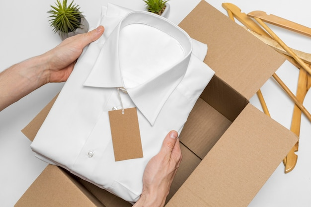 Vue de dessus personne mettant une chemise pliée dans une boîte
