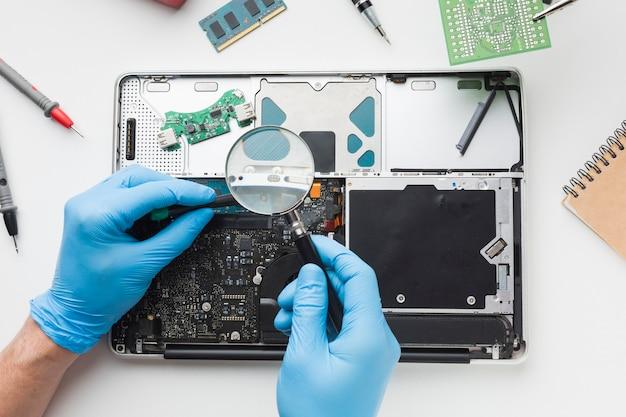 Vue de dessus personne réparant un ordinateur portable