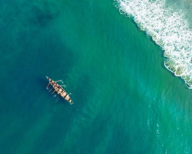 Vue de dessus de personnes dans un bateau pêchant sur la plage de varkala