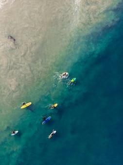 Vue de dessus de personnes avec des planches de surf nageant sur la plage de varkala