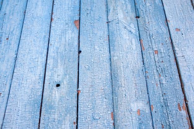 Vue de dessus en perspective de planches de bois patinées avec de la peinture bleue craquelée