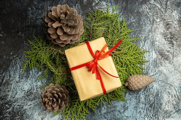 Vue de dessus petit cadeau attaché avec un ruban rouge sur des branches de pin pommes de pin sur une surface sombre