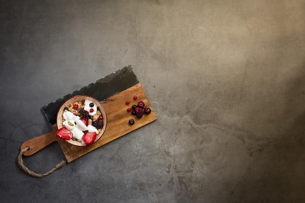 Vue de dessus d'un petit-déjeuner sain avec du muesli, du yogourt et des baies de saison sur un fond de béton