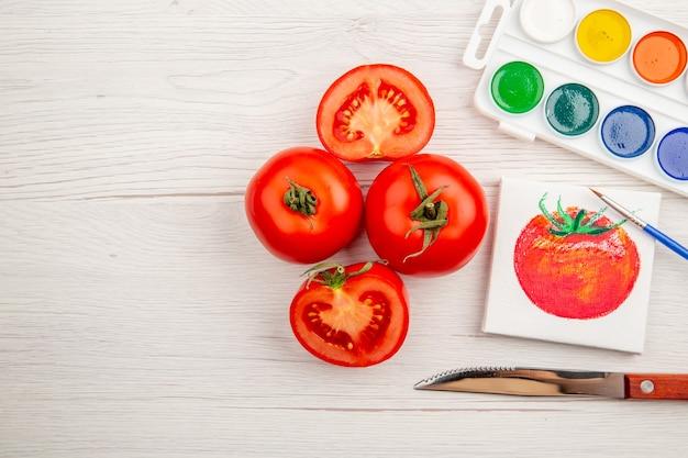 Vue de dessus petit dessin de tomate avec des tomates fraîches sur un bureau blanc