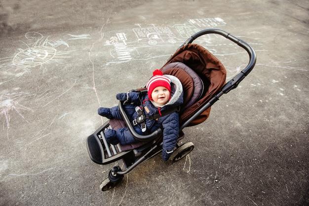 Vue de dessus sur le petit enfant souriant vêtu d'une combinaison chaude assis dans une poussette